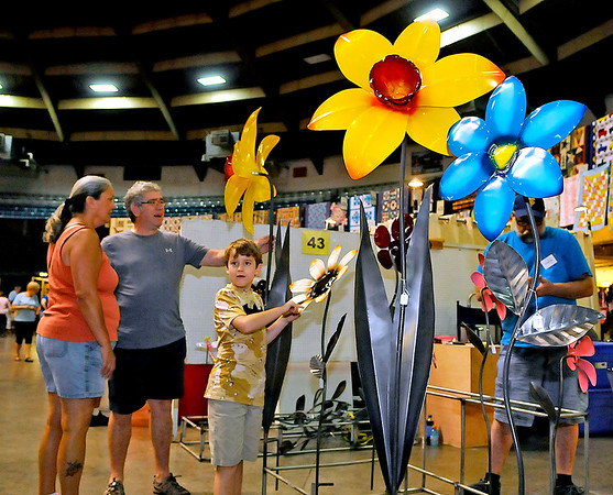 Brad Davis/The Register-Herald<br /> Fairdale residents Harvey, Rhonda and 8-year-old Cory Johnson marvel at the massive flowers at Steel Blooming Metal Flowers' booth, manned by owner and Charleston artist Joe Foley, inside the Beckley-Raleigh County Convention Center Saturday afternoon during the Appalachian Arts & Crafts Fair.