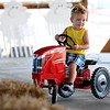 Rick Barbero/The Register-Herald<br /> Austin Runyon, 3, of Wharncliffe, riding a toy tractor at The WV State Fair in Fairlea.