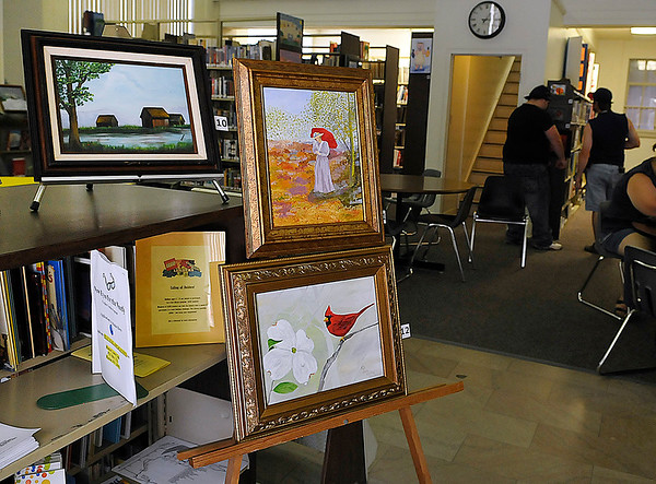 Brad Davis/The Register-Herald<br /> Art hangs on display at the Hinton Public Library during the State Water Festival Aug. 1 in Downtown Hinton.