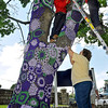 Brad Davis/The Register-Herald<br /> Cheryl Eccles-Clark, lower rigt, ties off some loose ends while Aspen Tree Service volunteers Cory Evans (left) and Roy Justice help a yarnbombing mix artists and Alzheimer's awareness advocates reach the upper portions of a tree in front of Jackie Withrow Hospital along Eisenhower Drive Friday afternoon. Many have already seen several of the multi-colored cozies around town, but this one is specifically themed in support of Alzheimer's awareness, with Alzheimer's Disease Awareness and Caregivers Month coming up in November.
