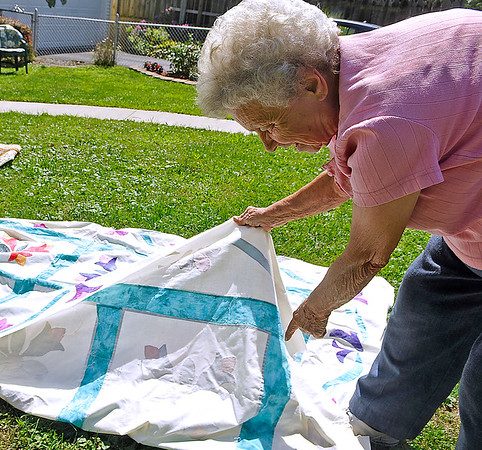 Brad Davis/The Register-Herald<br /> 82-year-old quilter Sadie Handyside shows off the tedious hand-stitching style she uses to make her creations outside of her High Circle Drive home near Oak Hill Friday afternoon. Her technique is a rarely used one by many of today's quilters. The results are elements of the quilt that appear to be glued on, but a closer look reveals that each little piece was hand-stitched. A quilt made in this way takes Handyside up to two years to finish.