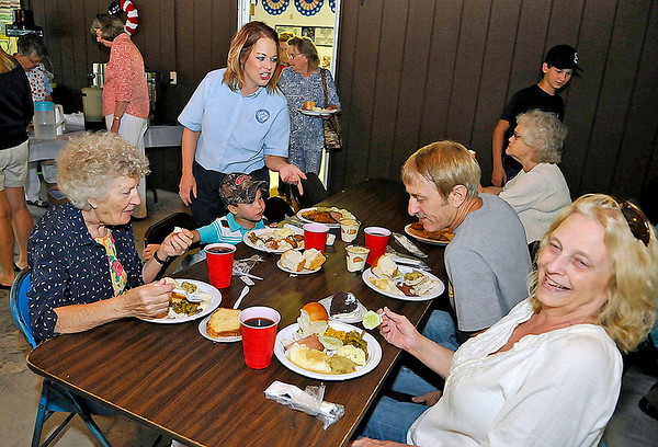 Brad Davis/The Register-Herald<br /> Debbie Lilly and her husband Larry (right), Pamela Lusk-Lilly (standing), four-year-old Jake, an original Lilly, and Polly Lilly (left) enjoy good times and a good meal together surrounded by scores of other Lilly's during the opening dinner of the annual Lilly Family Reunion Friday evening in Ghent. Hundreds upon hundreds of Lilly's and their kin from all over will be gathering today on the family grounds for another year of one of the world's largest family reunions.