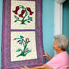 Brad Davis/The Register-Herald<br /> 82-year-old quilter Sadie Handyside shows off one her favorite works inside her High Circle Drive home near Oak Hill Friday afternoon. If you were to visit her, you'd notice the walls of her home are decorated with lots of her and other quilters' work. She quite handy with it too when it comes decorating, as this piece covers up her home's breaker box. She says she'd much rather look at a nice work of art than a plain old electric box.