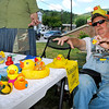 Brad Davis/The Register-Herald<br /> Hinton resident and rubber ducky whisperer Dwight Emrich, along with his wife Linda (hidden at left), ritualistically bestows good luck upon a table full of duckies bound for the New River as they man the sign-up table during the State Water Festival Saturday afternoon in downtown Hinton. The rubber ducky race takes place today at 4:00 with a cash prize, and if you hurry you might still be able to grab one of 700 race-ready duckies available.