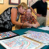 Brad Davis/The Register-Herald<br /> Beckley artist Miles Cushman, seated, shares some laughs with family friend Sandi Schroder (left) during a reception for his work at the Beckley Art Center's Cynthia Bickey Gallery Thursday evening. Art has played a major role in helping the now 38-year-old Cushman recover from a 1999 car accident that left him with a traumatic brain injury. The former Virginia Tech student has amassed volumes and volumes of work over the years during his recovery process, and Thursday's reception provided him the opportunity to share it with the community as he signed autographs, gave away some free work and met with fellow artists and friends from all over.