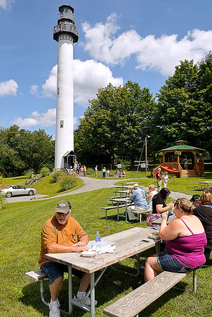 Brad Davis/The Register-Herald<br /> Visitors relax with good food and take in some live music at the Summersville Lake Retreat, as tours of the lighthouse go on in the background during the Summersville Lake Lighthouse Festival Saturday afternoon in Mount Nebo.