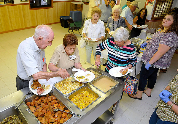 Brad Davis/The Register-Herald<br /> Family and kin from all over line up to get a hearty plate of food during the annual Lilly Family Reunion opening dinner Friday evening in Ghent.