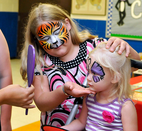 Brad Davis/The Register-Herald<br /> Two-year-old Virginia Dunbar has a look in the mirror as she checks out her face paint with her big sister Sarah, 9, during a launch party for the Imagination Library at Clear Fork District Elementary School August 22 in Artie.