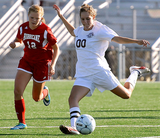 Brad Davis/The Register-Herald<br /> Woodrow Wilson's Rebekah Cook sends the ball downfield as Hurricane's Ann-Marie Ramey closes in Thursday evening at the YMCA Paul Cline Memorial Sports Complex.