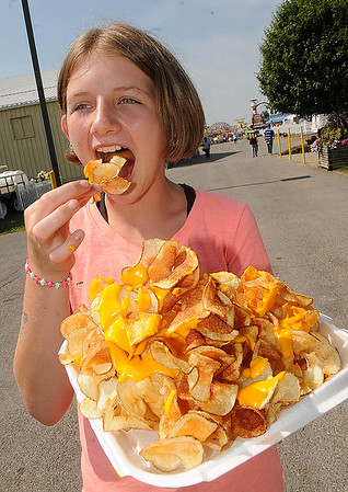 Rick Barbero/The Register-Herald<br /> Alisha Hedrick, 11, of Williamsburg, WV, eating a cheese patato fries at the State Fair of West Virginia in Fairlea.