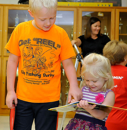 Brad Davis/The Register-Herald<br /> Two-year-old Virginia Dunbar and her big brother Noah, 10, look through a children's book about trains that she received during a launch party for the Imagination Library, a state reading and book program for children ages five and under Saturday morning at Clear Fork District Elementary School in Artie. Parents brought their young children out to sign up to receive books in the mail every month, get their faces painted if they wanted to and everyone who signed up received several goodies including frisbees and healthy snacks.