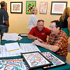 Brad Davis/The Register-Herald<br /> Beckley artist Miles Cushman, seated, shares some laughs with friend C.R. Allen (kneeling) as attendees browse his work on the wall behind him during a reception for Cushman's work at the Beckley Art Center's Cynthia Bickey Gallery Thursday evening. Art has played a major role in helping the now 38-year-old Cushman recover from a 1999 car accident that left him with a traumatic brain injury. The former Virginia Tech student has amassed volumes and volumes of work over the years during his recovery process, and Thursday's reception provided him the opportunity to share it with the community as he signed autographs, gave away some free work and met with fellow artists and community members.