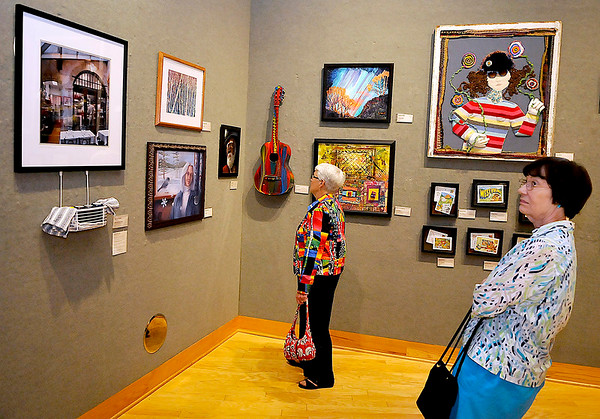 """Brad Davis/The Register-Herald<br /> Art enthusiasts Pat Roberts (right) and Nancy Moran view works on display Sunday afternoon at Tamarack's newest juried exhibit, """"Transforming Tradition,"""" which runs until September 27."""