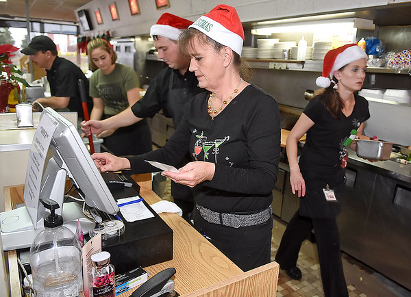 Brad Davis/The Register-Herald<br /> Omelet Shoppe employee Kelley Spangler works the cash register as fellow employees engage in the usual hustle and bustle around her while they work a Christmas day shift at the Harper Road restaurant Friday afternoon.