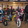 Brad Davis/The Register-Herald<br /> From left, three-year-old Hunter, 6-year-old Thomas and 8-year-old Amelia Mullins are ready to ride off with new bikes as their mother Amanda, right, looks on during Mac's Toy Fund Party Saturday morning at the Beckley-Raleigh County Convention Center.