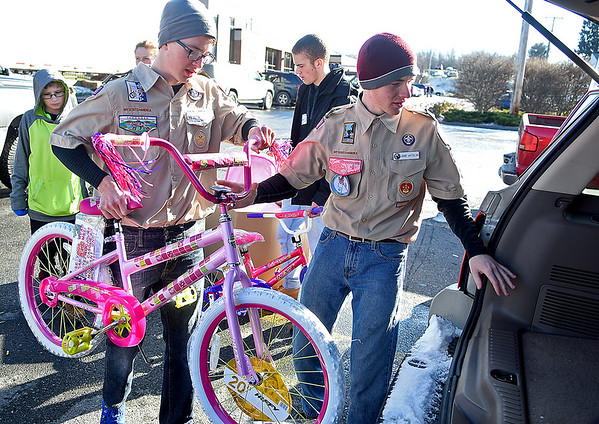Brad Davis/The Register-Herald<br /> Boy Scout volunteers from Troop 3 (Beckley) Pierson Lintala, left, and Jack Antolini load a bicycle into the back of a patron's vehicle during Mac's Toy Fund Party Saturday morning at the Beckley-Raleigh County Convention Center.