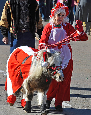 Brad Davis/The Register-Herald<br /> Mrs. Claus walks with a miniature horse during Beckley's annual Christmas Parade Saturday afternoon.