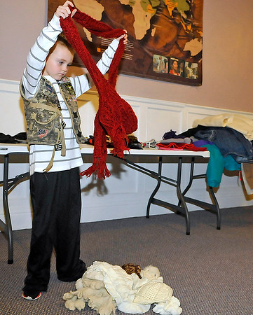 Brad Davis/The Register-Herald<br /> Seven-year-old Chance Lipford sorts and divides donated clothing items Thursday night at the House of Worship.