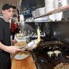 Brad Davis/The Register-Herald<br /> Omelet Shoppe cook Jeff Thomas mans the grill as he and fellow employees work a Christmas day shift at the Harper Road restaurant Friday afternoon.