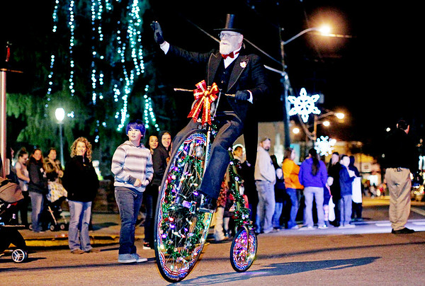 """Chris Jackson/The Register-Herald<br /> A member of the Oak Hill Christmas parade waves to the crowd as he pedals his Holiday adorned """"penny-farthing"""" or big-wheel bicycle down Main St. during their annual parade in Oak Hill on Thursday."""