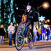 "Chris Jackson/The Register-Herald<br /> A member of the Oak Hill Christmas parade waves to the crowd as he pedals his Holiday adorned ""penny-farthing"" or big-wheel bicycle down Main St. during their annual parade in Oak Hill on Thursday."