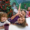Brad Davis/The Register-Herald<br /> Four-year-old Shelby (left) hangs out as 5-year-old sister Katelyn and 6-year-old brother Dylan Pruyne (middle) goof off and pose for the camera during a Christmas dinner at the Pinehaven Center Friday afternoon. Four-year-old Lauren Pruyne and Vanessa Hill-Ruff (background right) can also be seen enjoying dinner.