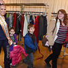 Brad Davis/The Register-Herald<br /> Tonia Bennett (right) leads her children Earle, 6, and Autumn, 4, along with new coats after Shady Spring High School cheerleader and current Miss Raleigh County Shyanne Boothe (left) helped pick them out during Mac's Toy Fund Party Saturday morning at the Beckley-Raleigh County Convention Center.
