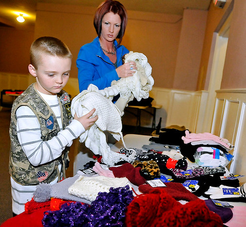 Brad Davis/The Register-Herald<br /> Seven-year-old Chance Lipford sorts and divides donated clothing items with the help of his mother Keri Thursday night at the House of Worship.