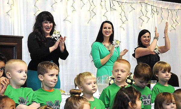 """Tammy Hancock, left, wife of the late Mel Hancock and his two daughters, Ann Elizabeth Hancock and Alisa Evans, clap after the YMCA Happy Kids Preschool sang, God Bless America during the """"Spirit of Beckley"""" awards fundraiser dinner held at the Beckley-Raleigh County Convention Center Monday night. This year's award recipient was the late Mel Hancock."""