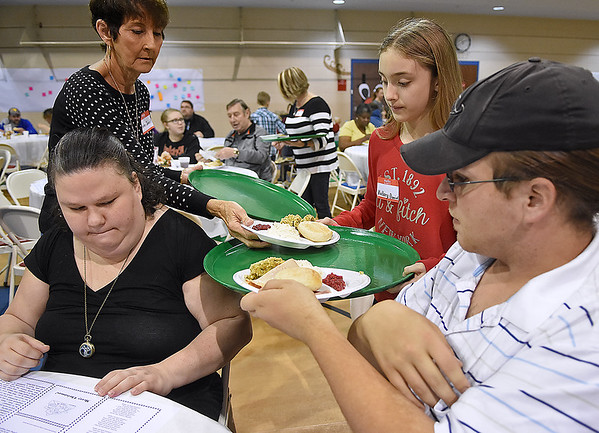 Brad Davis/The Register-Herald<br /> Beckley residents Sean Howard, far right, and Heather Chapman, left, have hearty plates of ham, turkey and mashed potatoes brought to them by volunteers Helen and 11-year-old Mallory Daniel during United Methodist Temple's annual community Christmas dinner Friday morning inside The Place.