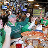 Brad Davis/The Register-Herald<br /> Marshall fans (from left) Chase Mooney, Dwight Bellomy, Carolyn Fields (hidden behind Dwight's arm) and Donnie Jones (end of table, arm raised) among others celebrate as the Thundering Herd kicks a field goal in the St. Petersburg Bowl against Connecticut during a watch party at Calacino's Saturday afternoon. The Thundering Herd went on to win the game 16-10, sending fans home happy with a fifth straight bowl win.