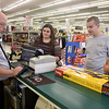 Brad Davis/The Register-Herald<br /> Store manager Ronnie Boyd, left, punches a few buttons on the register as he helps Beckley residents Karen Griffith (2nd from left), her son Cameron and young Jeremiah Allen, right, exchange a Daisy youth crossbow for a new one after the original had a faulty part Saturday afternoon at Magic Mart in the Beckley Plaza Mall. While the day after Christmas is usually a major return and exchange day for retailers, Boyd said Saturday was unusually slow in that regard and that his store had seen most exhanges occur in the days leading up to Christmas.
