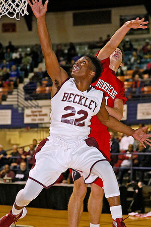 Brad Davis/The Register-Herald<br /> Woodrow Wilson's Isaiah Francis leaps to tip in a rebound before Hurricane's Braxton Dobert can stop him during the Flying Eagles' win over the Redskins Friday night at the Beckley-Raleigh County Convention Center.