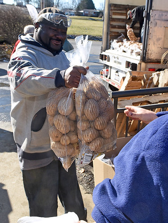 Brad Davis/The Register-Herald<br /> Volunteer Ron Blanks hands out bags of potatoes to exiting patrons during Mac's Toy Fund Party Saturday morning at the Beckley-Raleigh County Convention Center. The West Virginia Department of Agriculture provided around 32,000 pounds of state-grown potatoes to be handed out to anyone who wanted some as they left, and Bays Services provided the truck to distribute them from.