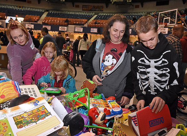 Brad Davis/The Register-Herald<br /> 12-year-old Dakota Stoots (far right) and his mother Monica pick out used toys while volunteer Christy Whittaker (far left) helps 9-year-old Cheyenne Bledsoe (2nd from left) and 6-year-old Elizabeth Holcomb (3rd from left) sort through items during Mac's Toy Fund Party Saturday morning at the Beckley-Raleigh County Convention Center.