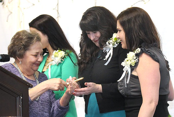 """Lynn O'Brien, left, presents the key to Beckley to Mel Hancocks wife, Tammy Hancock, during the """"Spirit of Beckley"""" awards fundraiser dinner held at the Beckley-Raleigh County Convention Center Monday night. Also pictured Mel's daughters, Ann Elizabeth Hancock and Alisa Evans."""