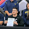 Brad Davis/The Register-Herald<br /> Westside athlete Justin Cogar holds up his signed letter of intent to play football for West Virginia University flanked by his parents Noel and Lori (lower left), along with his sister Jordan, upper right, and head coach Larry Cook (hidden background left) during his national signing day ceremony Wednesday afternoon in Clear Fork. The Renegades' quarterback will switch over to the tight end position and is expected to begin working with the Mountaineers this summer.