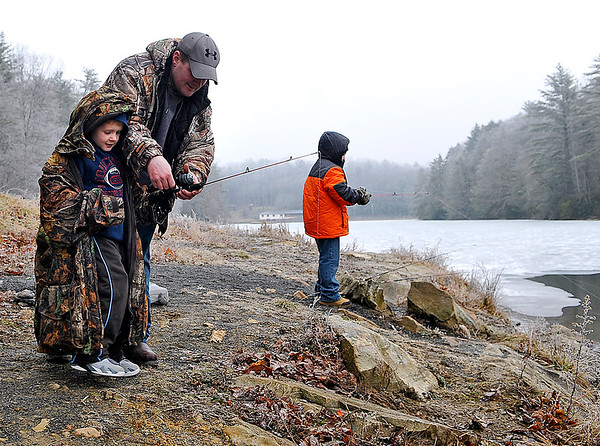 Brad Davis/The Register-Herald<br /> Five-year-old Oak Hill resident Kaiden Manns, left, gets some help from his dad John as he prepares to cast his fishing line while his older brother Isaiah (far right), 8, waits for something to bite Tuesday afternoon at Little Beaver State Park. The cold, literally icy weather wasn't a deterrent for these outdoor enthusiasts, and neither was the sight of a nearly completely frozen lake. A short walk along the paved trail side leads to a nice little hidden section of unfrozen water on the back end of the lake where the Manns' decided to fish. The walk paid off, as the trio had already caught a couple of rainbow trout in just the first half hour.