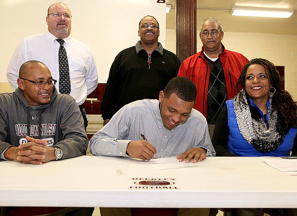 Brad Davis/The Register-Herald<br /> Woodrow Wilson's Noah Hancock signs his letter of intent to play football at Concord University during his national signing day ceremony Wednesday afternoon in Beckley. Surrounding him are his parents William (lower left), mother Kristin Anderson (lower right), head coach John Lilly (upper left), and grandfathers William Pace (upper middle) and Rev. Nelson Staples III.