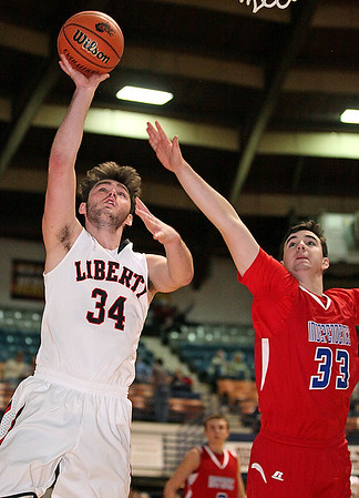 Brad Davis/The Register-Herald<br /> Liberty's Trevor McGhee scores as he drives to the basket against Independence's Logan Kelly Saturday afternoon at the Beckley-Raleigh County Convention Center.