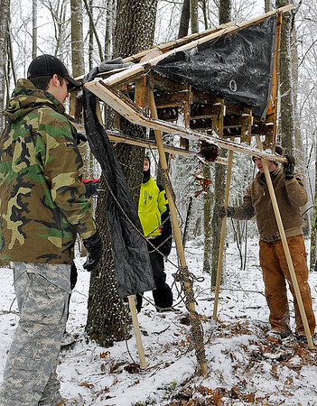 """Brad Davis/The Register-Herald<br /> Beckley Troop 3 Scouts Luke Jones, far right, Carter (middle behind tree), and Chad Nay, left, work to elevate their sled at station seven of 10 Saturday. The """"Save Your Sled"""" station tested the scouts ability to get their sled out of harm's way in a scenario where their patrol encountered an emergency along the patrol. The derby course consisted of 10 stations where various Boy Scouts skills were tested, such as knots and lashing, orienteering, first aid and shelter building, among others."""