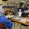 Brad Davis/The Register-Herald<br /> American Legion Post 32 Commander Ron Jennings (2nd from left in grey) looks on while Jason Jennings, far left, mans the baked goods table as area residents shop and mingle during a fundraising event Saturday afternoon that featured a NASCAR simulator built into a car that driven by Kevin Harvick in 2007.
