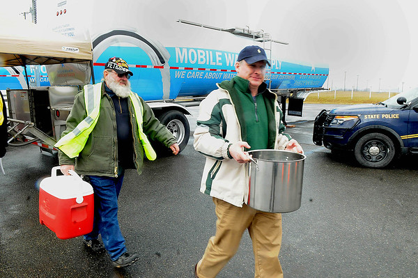 Rick Barbero/The Register-Herald<br /> Hank Fischer, Monroe CERT Team, left, helps Jeff Vickers, of Lewisburg, right, carry water back to his vehicle at the State Fair grounds in Fairlea were they have two mobile water tanks.