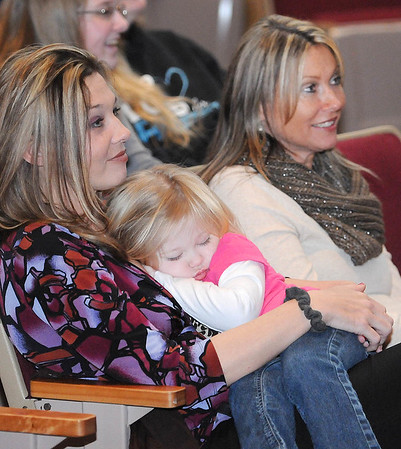 Rick Barbero/The Register-Herald<br /> Angel Hodge, of Beckley, left, holding her daughter Piper Hodge, 2, and Trica Nish, of Beckley, watch the Raleigh County Middle School Spelling Bee held at Woodrow Wilson H.S. Auditorium Wednesday morning.