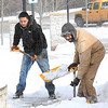 Rick Barbero/The Register-Herald<br /> Raymond Edmonds, left, and Kevin Leftwich, both with the Beckley Board of Public Works, shovel snow off the walk in front of Beckley Intermodal Gateway parking garage.