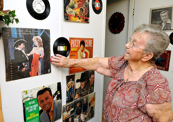 Brad Davis/The Register-Herald<br /> Dickens' sister Edna Allen points out one of the only albums she had difficulty tracking down for her collection, his Country Music Hall of Fame performance in 1983.