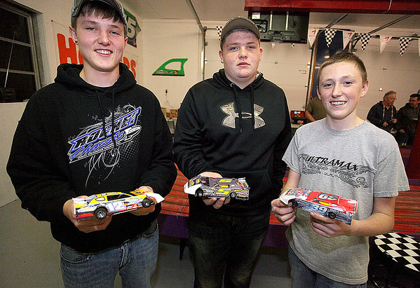 """Brad Davis/The Register-Herald<br /> Young slot car racers (from left) R.J. Smith, Gray Bowyer and Henry Hornsby III show off their cars Saturday night. While all three regularly achieve racing glory at Dirt Slotz, Hornsby, 15, is an actual race car driver who pilots a """"crate late model"""" dirt car that looks exactly like the slot car he's holding. His Dirt Slotz car is a replica of the one he drives for real at places like the Beckley Motor Speedway and other tracks he's raced at along the East coast over his two-year career."""