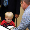 Brad Davis/The Register-Herald<br /> Two-year-old Beckley resident Bryson Harmon gets an autographed football from New Orleans Saints head coach Sean Peyton following the Big Atlantic Classic Banquet Sunday afternoon at the Beckley-Raleigh County Convention Center.
