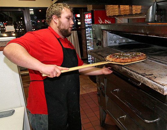 Brad Davis/The Register-Herald<br /> Pizza artist and Padrino's employee Robbie Wotter pulls a freshly baked pie from the oven as he works at the restaurant's Beckley Crossing location Sunday night.