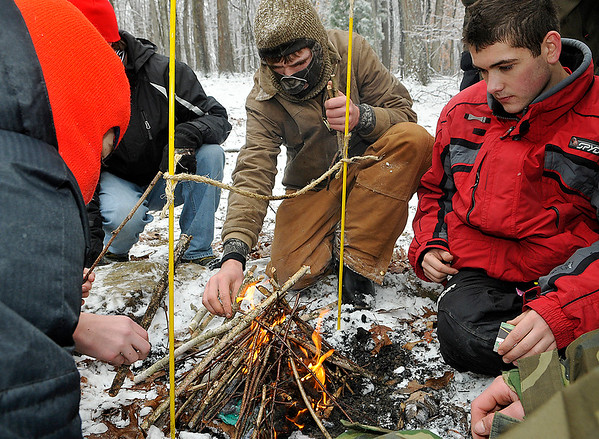 Brad Davis/The Register-Herald<br /> Beckley Troop 3 Scouts Luke Jones, middle, Andrew Barbera, right, and the rest of their group gather around the fire starting station, the fifth on the course, as they try to light a fire with natural materials strong enough to burn through the rope above it within 10 minutes. The derby course consisted of 10 stations where various Boy Scouts skills were tested, such as knots and lashing, orienteering, first aid and shelter building, among others.